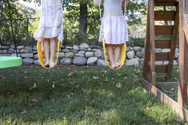 Low section of sisters standing on swings at playground - CAVF52337