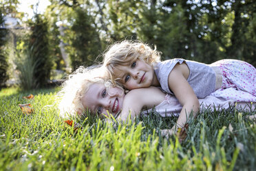 Portrait of sisters lying on grassy field at park - CAVF52340