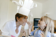Happy mother and daughter playing at home putting on chef's hat - KNSF05042