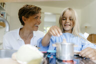 Happy mother and daughter playing with toy kitchen at home - KNSF05045