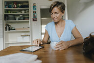 Woman sitting at table at home with cup of coffee and tablet - KNSF05051