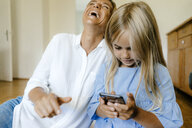 Laughing mother and daughter looking at smartphone - KNSF05060