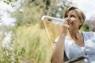 Portrait of woman sitting in garden on chair - KNSF05066