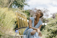 Relaxed woman sitting in garden on chair with closed eyes - KNSF05069