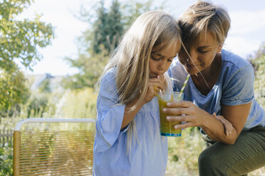 Mother and daughter sharing a smoothie in garden - KNSF05090