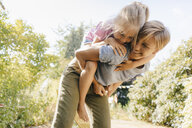 Happy mother carrying daughter piggyback in garden - KNSF05099