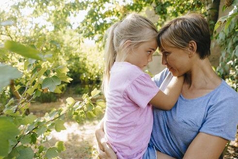 Mother carrying daughter in garden - KNSF05102