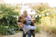 Happy father carrying family piggyback in garden - KNSF05108