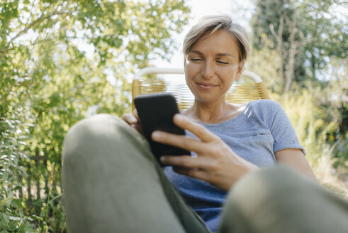 Woman sitting in garden on chair using cell phone - KNSF05111