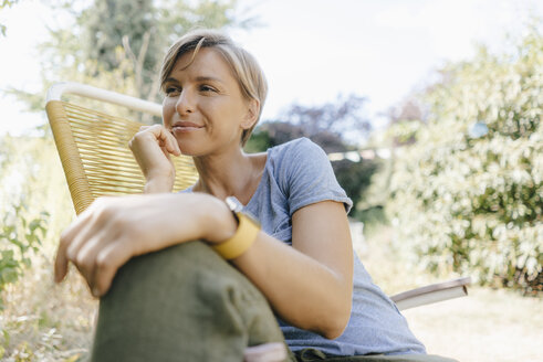Woman sitting in garden on chair - KNSF05123