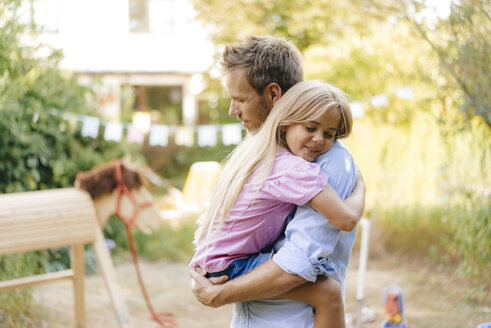 Father cuddling with daughter in garden - KNSF05126