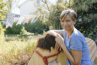 Portrait of smiling woman with wood horse in garden - KNSF05138