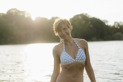 Portrait of smiling woman wearing a bikini in a lake - KNSF05153