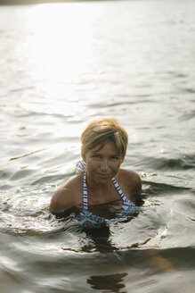 Portrait of smiling woman swimming in a lake - KNSF05156