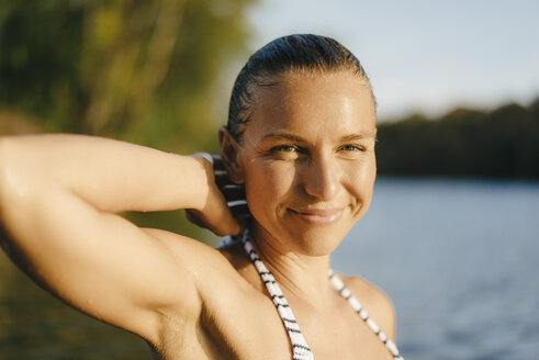 Portrait of smiling woman with wet hair at a lake - KNSF05159