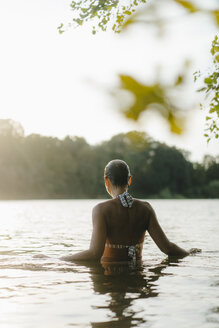Rear view of woman in a lake at sunset - KNSF05165