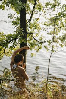 Rear view of woman wearing a bikini at tree trunk at a lake - KNSF05171