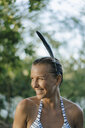 Portrait of happy woman with wet hair wearing feather in her hair - KNSF05177
