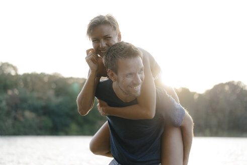 Happy man carrying girlfriend piggyback at a lake - KNSF05183