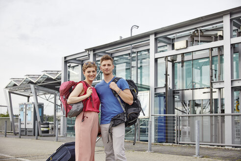Portrait of smiling couple outside airport - RHF02210