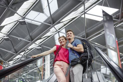 Happy couple on escalator at the airport - RHF02216