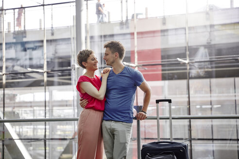 Smiling couple standing at the airport - RHF02219