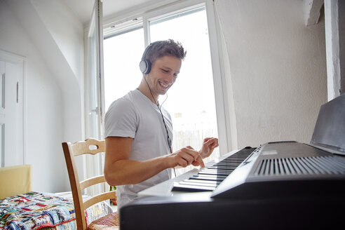 Smiling young man at home wearing headphones playing digital piano - RHF02267