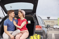 Happy young couple sitting in car boot at the airport - RHF02270
