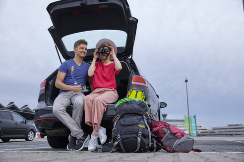 Happy young couple with snorkeling equipment sitting in car boot at the airport - RHF02273