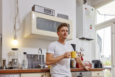 Smiling young man at home having a coffee break in kitchen - RHF02276