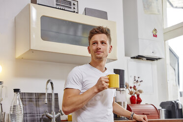 Smiling young man at home having a coffee break in kitchen - RHF02279