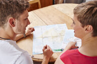 Young couple sitting at table at home with map - RHF02288