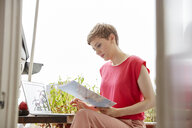 Woman sitting on balcony at home with laptop and map - RHF02291
