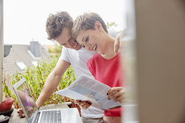 Happy couple on balcony at home with laptop and map - RHF02294