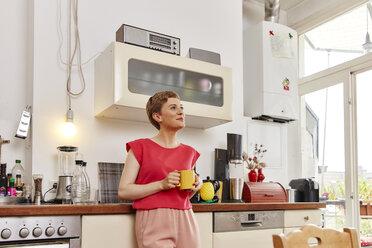 Smiling woman having a coffee break in kitchen - RHF02297