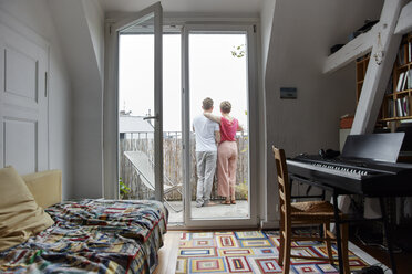 Rear view of couple standing on balcony at home - RHF02300