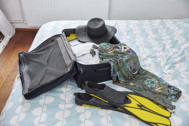 Suitcase with summer vacation utensils on bed - RHF02303