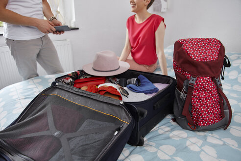 Happy couple packing suitcase for summer vacation on bed - RHF02306