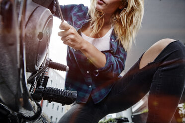 Young woman working on motorcycle - RHF02315