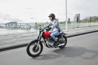 Germany, Cologne, young woman riding motorcycle on bridge - RHF02321