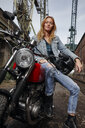 Portrait of confident young woman on motorcycle - RHF02327