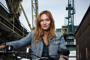 Portrait of confident young woman on motorcycle - RHF02333