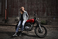 Portrait of confident young woman with motorcycle - RHF02336