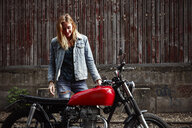 Smiling young woman standing next to motorcycle - RHF02339