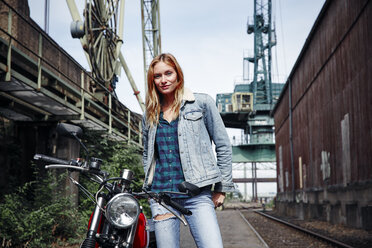 Portrait of confident young woman with motorcycle - RHF02342