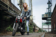 Portrait of confident young woman getting on motorcycle - RHF02345