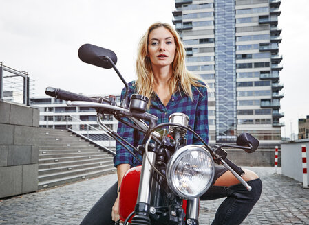 Portrait of confident young woman on motorcycle - RHF02348