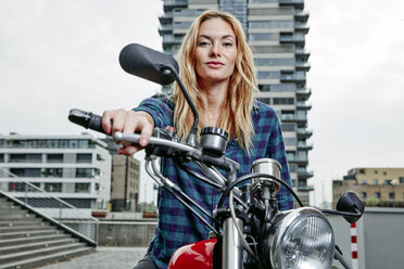 Portrait of confident young woman on motorcycle - RHF02351
