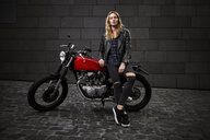Portrait of confident young woman with motorcycle - RHF02354