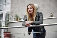Confident young woman wearing biker jacket leaning on balcony railing - RHF02366